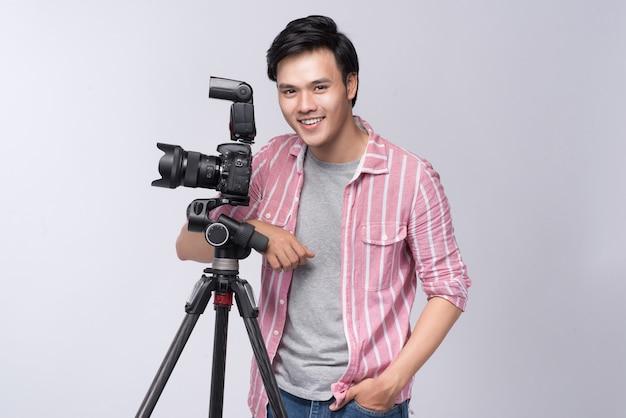 스튜디오에서 일하는 동안 디지털 카메라를 들고 있는 젊은 아시아 사진작가
