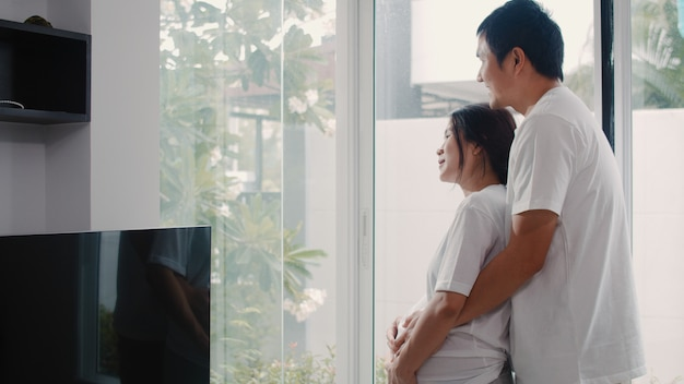 Young asian pregnant couple hug and holding belly talking with their child. mom and dad feeling happy smiling peaceful while take care baby, pregnancy near window in living room at home . Free Photo