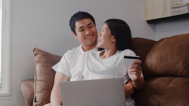 若いアジアの妊娠カップルの自宅でのオンラインショッピング。ママとパパは、自宅のリビングルームのソファに横たわっている間、ラップトップテクノロジーとベビー用品を購入するクレジットカードを使用して幸せを感じています。