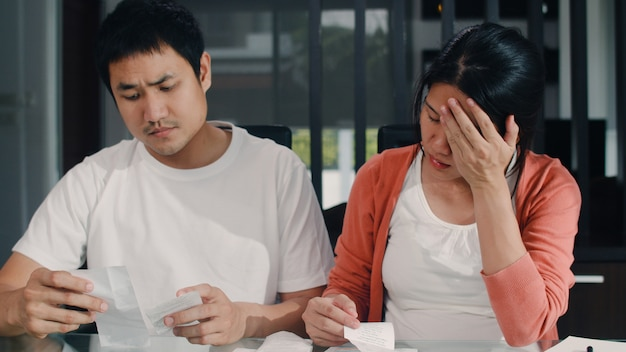 Young asian pregnant couple records of income and expenses at home. mom worried, serious, stress while record budget, tax, financial document working in living room at home .
