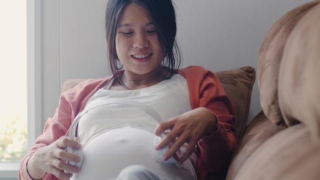 Молодая азиатская беременная женщина используя телефон и наушники играет музыку для младенца в животе. мама чувствуя счастливый усмехаясь позитив и мирное пока заботьтесь ребенок лежа на софе в живущей комнате дома.