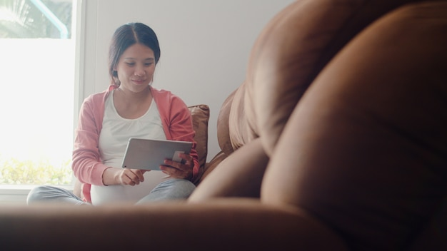 Young asian pregnant woman using tablet search pregnancy information. mom feeling happy smiling positive and peaceful while take care her child lying on sofa in living room at home .