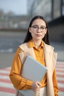 通りを渡って真剣に見える眼鏡の若いアジアのきれいな女性