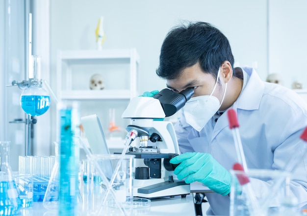 Young asian researcher using modern microscope in laboratory.