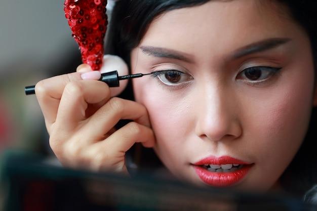 아름 다운 얼굴에 아이 섀도 적용하는 젊은 아시아 산타 여자