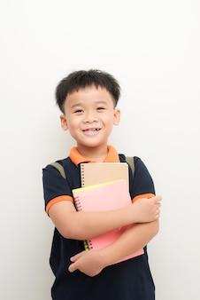 Молодой азиатский школьник, держа тетради, изолированные на белом фоне