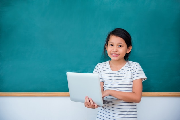Young asian schoolgirl holding laptop computer and smiles in front of chalkboard