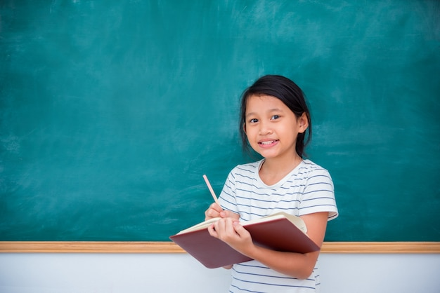 Young asian schoolgirl smiling in front of chalkboard