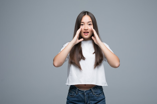 Young asian scream loud isolated on gray background