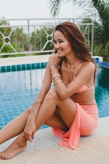 ピンクのビキニで若いアジアのセクシーな美しい女性、スイミングプールに座って、スリムな日焼けした肌、ファッショングラマーアクセサリー、ブレスレット、リラックスした、笑顔、官能的な、夏休み