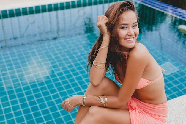 Молодая азиатская сексуальная красивая женщина в розовом бикини, сидящая у бассейна, стройная, загорелая кожа, гламурные аксессуары, браслеты, расслабленная, улыбающаяся, чувственная, летние каникулы