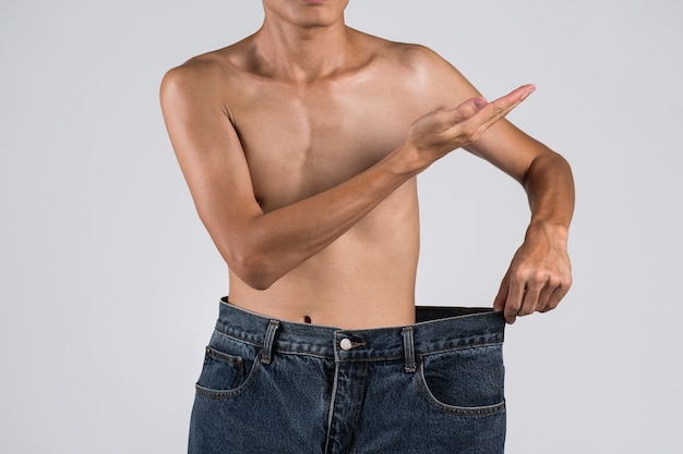 Young asian shirtless man with over-sized his old jeans after lose weight and hand up