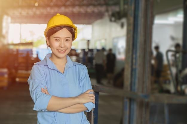 물류 창고 초상화에서 수석 엔지니어 매니저로 일하는 젊은 아시아 똑똑한 여성이 팔짱을 끼고 웃고 있습니다.