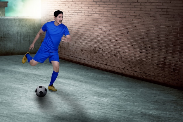 Young asian soccer player practicing soccer