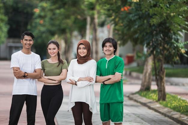 Молодые азиатские люди спорта пересекли руку