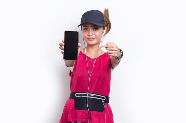 白い背景の上の携帯電話を示す若いアジアのスポーティな女性