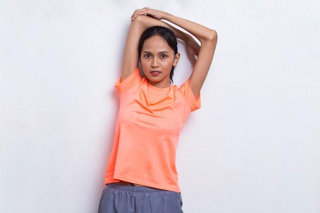 白い背景でストレッチをしている若いアジアのスポーティな女性