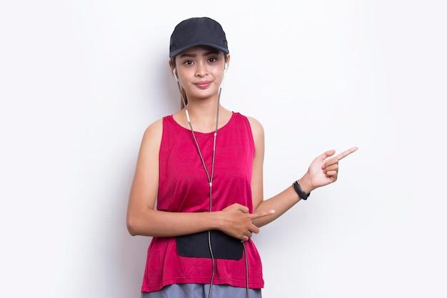 若いアジアのスポーティな女性が白い背景の上の空のスペースに指を指しています