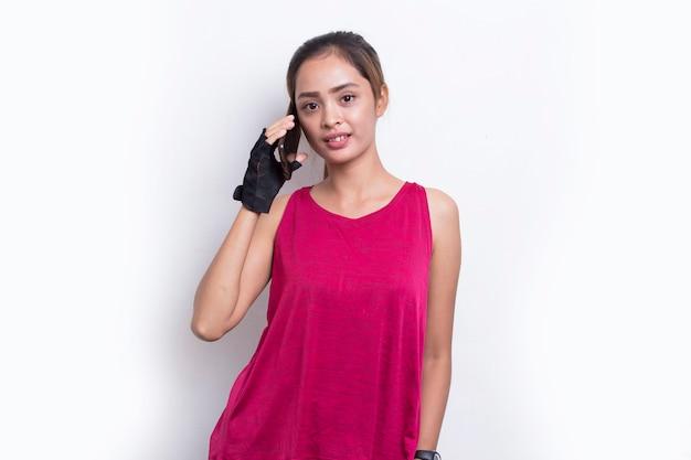 白い背景の上の携帯電話を使用して若いアジアのスポーティな女性