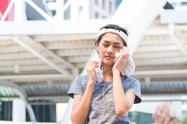 Молодая азиатская спортивная женщина, вытирая пот после завершения упражнения с белым полотенцем.