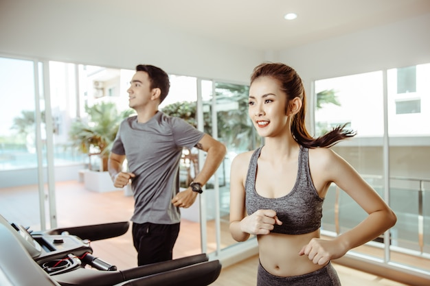 Young asian sporty women run on machine in the gym centre