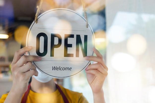 Молодая азиатская женщина персонала в защитной маске поворачивает открытую вывеску на стеклянной двери в современном кафе-кафе, гостиничном обслуживании, кафе-ресторане, розничном магазине, концепции владельца малого бизнеса