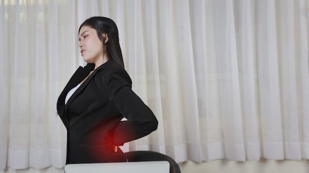 Молодая азиатская женщина подчеркнула, что чувствует боль или испытывает проблемы с болью в спине после слишком долгой работы за компьютером. концепция офисного синдрома