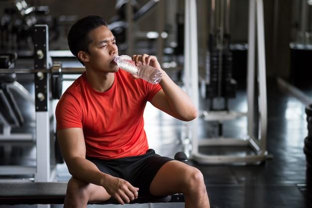젊은 아시아의 강한 근육질의 잘생긴 남자는 운동을 마치고 휴식을 취한 후 피트니스 체육관에서 물을 마십니다. 보디 빌딩 및 건강한 라이프 스타일 개념입니다.