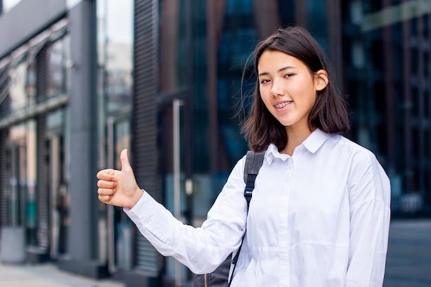 親指を現して、屋外のバックパックと白いシャツで笑顔の若いアジア学生の女の子。
