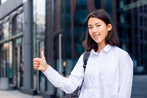 Young asian student girl showing thumb up and smiling outdoors in white shirt with backpack.