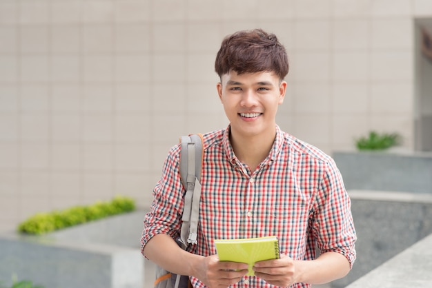 Молодой азиатский студент внутри здания университета