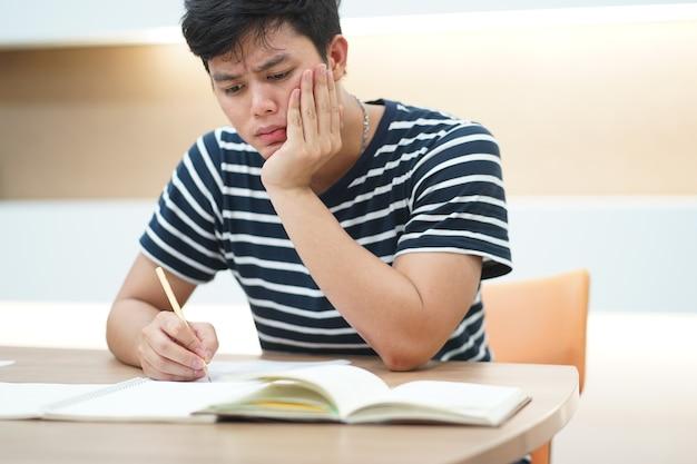 若いアジアの学生の男は、読書と試験のプレテスト中にストレスを感じる