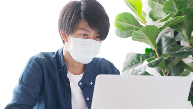 Young asian student man wearing protection mask working with laptop computer while online study