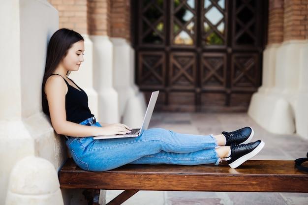コンピューターのラップトップで大学のキャンパスで若いアジア学生