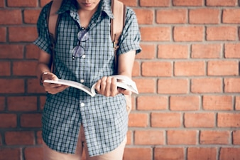 Young asian student studying in library with brick wall background.