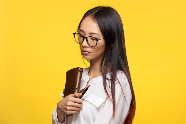 Молодая азиатская студенческая женщина позирует