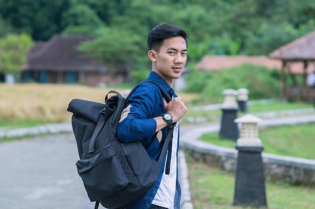 公園に立っているランドセルを持ったカジュアルな服装の若いアジアの学生。