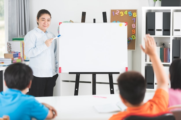 Young asian teacher ask question young kids in classroom .