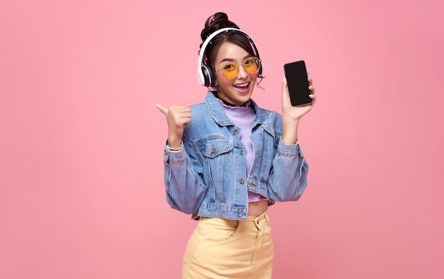 Молодая азиатская предназначенная для подростков женщина показывает умный телефон, она слушает музыку в наушниках, изолированных на розовом фоне.