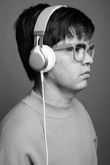 Young asian teenage boy wearing eyeglasses while listening to music