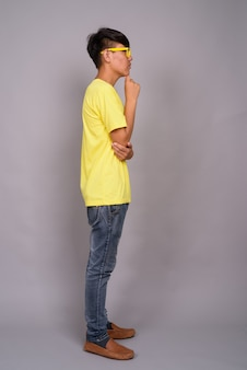Молодой азиатский подросток в желтой рубашке и очках на серой стене