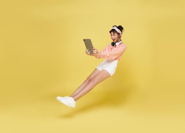 黄色の壁に隔離空中に浮かんでいるコンピューターのラップトップを持っている若いアジアの10代の少女の手。高速インターネットの概念。