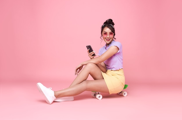 Young asian teenage girl sitting on skateboard and holding smartphone on pink wall.