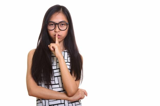 唇に指を持つ若いアジアの10代のオタクの女の子