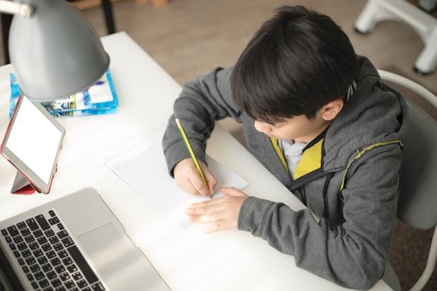 Young asian teenage student doing homework .
