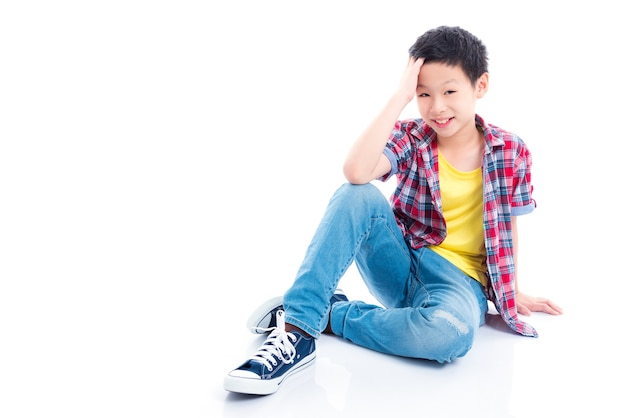 若いアジアのティーンエイジャーの男の子は、座って、白い背景に笑顔