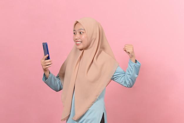 携帯電話を持って勝利のジェスチャーをしている若いアジアのティーンエイジャー、幸せはピンクの背景で隔離の特別な贈り物をオンラインで取得します