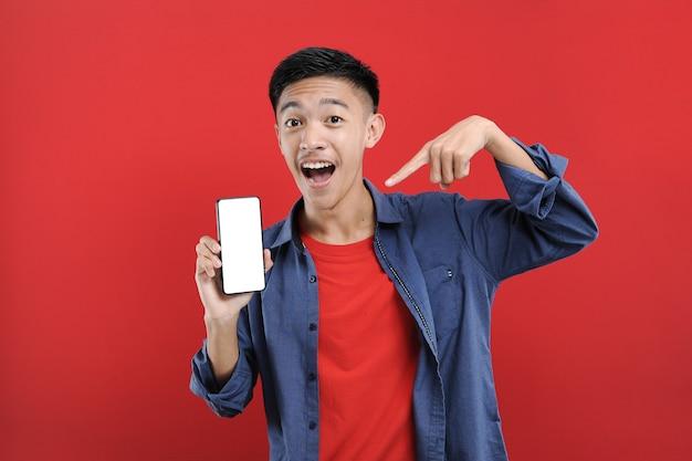 携帯電話を持って勝利のジェスチャーをしている若いアジアのティーンエイジャー、幸せは赤でオンラインで特別な贈り物を得る