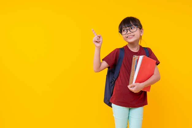 Young asian thai girl student in red shirt with shoulder bag pointing up
