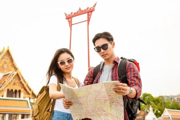 Young asian tourist couple looking at the map while traveling in bangkok thailand